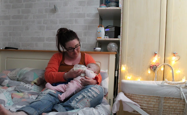 mother feeding baby with a bottle in bed