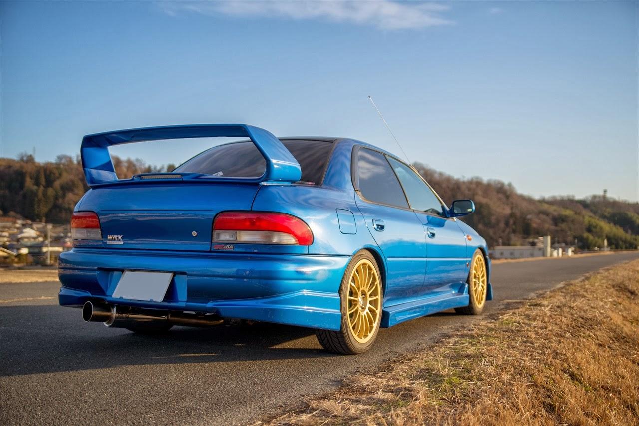 Subaru Impreza WRX STi, kultowe samochody, sportowe auta z duszą, napęd na cztery koła, silnik boxer, rajdówka, japońska motoryzacja, galeria zdjęć, niebieska, złote felgi, tył