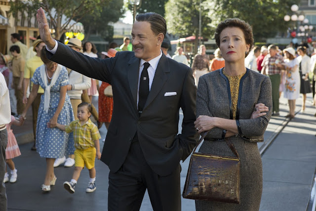 Walt Disney and PL Travers tour Disneyland.  Disney, played by Tom Hanks, gleefully waves hello to the crowds.  Travers, played by Emma Thompson, looks unimpressed.