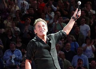 Bruce Springsteen in 2013 in front of a concert audience, pointing to the sky with a microphone in his left hand.