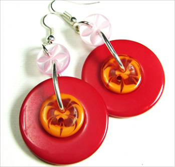Edgy drop earrings have big red buttons hanging from pink flower buttons