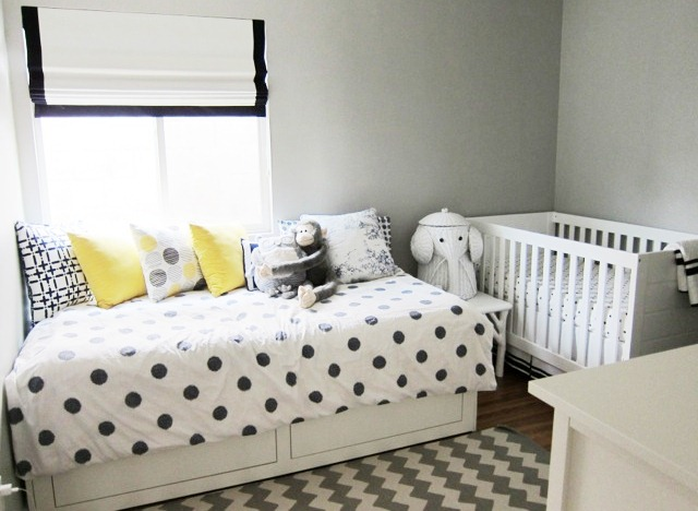 nursery with black and white chevron patterned rug, a twin bed with underbed storage and polka dot bedding, Nbaynadamas accent pillows, a white crib and an elephant hamper