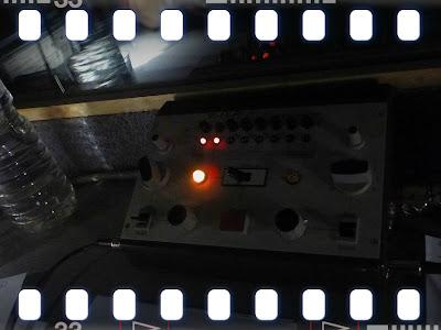 Dolmetschpult in dunkler Umgebung, nur drei Lämpchen brennen: Das Mikro ist offen, wir arbeiten ins Französische und Englische (Nachbarkabine)