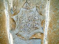 Escut amb inscripció a la clau del portal del Prat