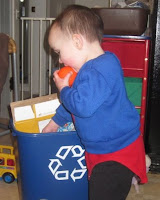 toddler putting things in recycling bin