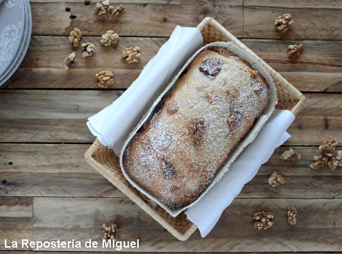 Pan en una cesta de mimbre vista desde una perspectiva aérea sobre una mesa de madera y unas cuantas de nueces sobre ella.
