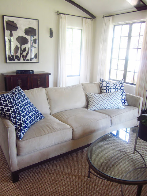 beige sofa with COCOCOZY accent pillows, oval glass table with metal legs on a woven rug. Behind it is a modern flower print and a small cabinet.