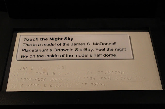 "In large print and Braille reads the following exhibit signage: ""Touch the Night Sky.  This is a model of the James S. McDonnell Planetarium's Orthwein StarBay.  Feel the night sky on the inside of the model's half dome."""