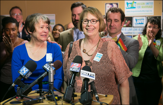 Two women stand before several news outlet microphones with a crowd of people behind them. Oregon United for Marriage banners and posters are on the wall in the background.