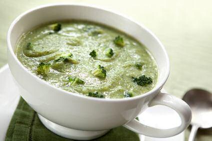 Een kom dikke broccoli courgettesoep met stukjes gestoomde broccoli