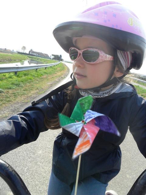 Casco, occhiali, girandola e bicicletta