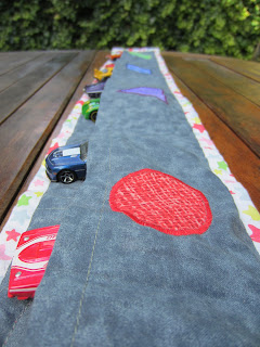 toy cars in pockets in the back of quilted colour matching table runner