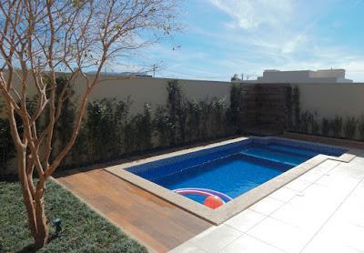 O quintal da casa foi agraciado com uma piscina, com ducha externa no vértice direito do terreno e tratamento paisagístico nos muros de fechamento do lote.