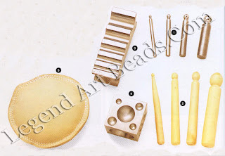 1 Metal doming punch;  2 wooden doming punches;  3 stainless steel swage block the doming punch handles are used in conjunction with the swage block; 4 stainless steel doming block;  5 leather sandbags used to give a resistant but soft backing.