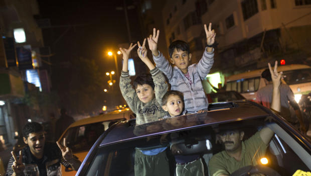 "Cheering Gazans and Palestinians emerged from their homes after a week, flooding the streets in wild celebration. Gunmen fired in the air, and chants of ""God is Great"" echoed from mosque loudspeakers. Residents hugged and kissed in celebration, while others distributed candy and waved Hamas flags."