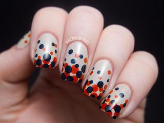 unha decorada na cor branca com bolinhas laranjas e azuis escuro