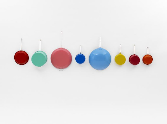 8 brightly painted colour saucepans on a white wall