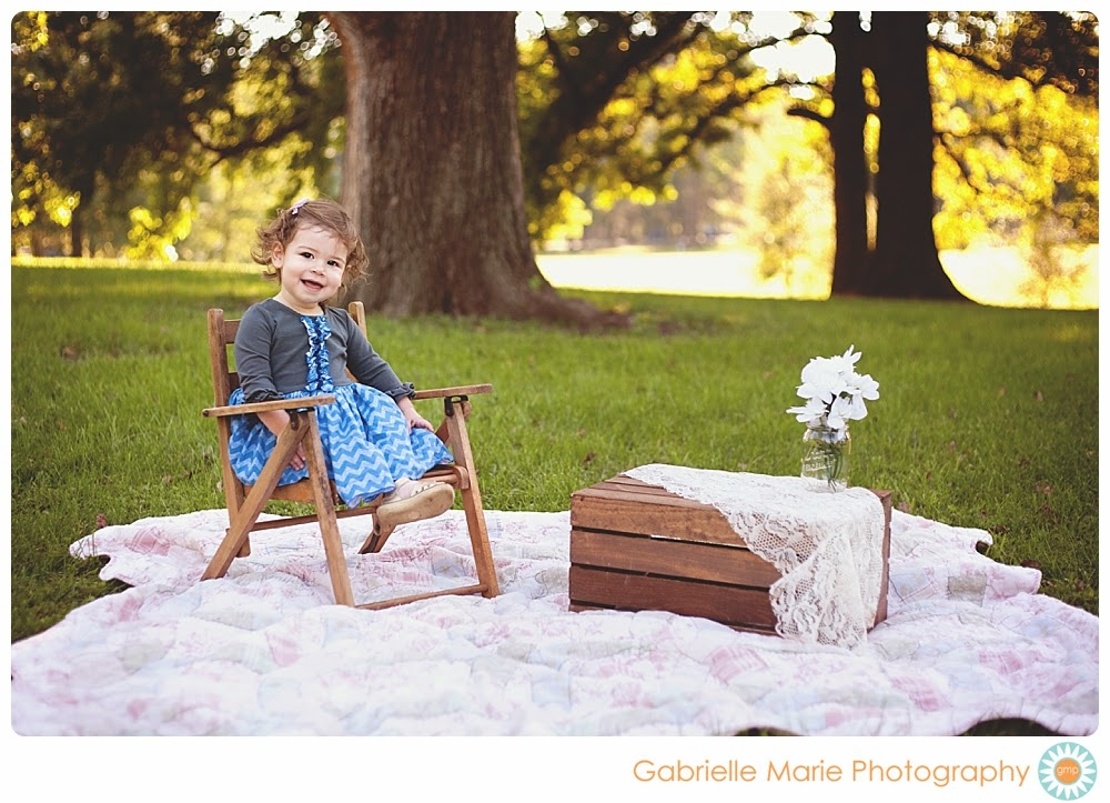 Sweet smiling 18 month girl sits in a chair on a quilt in Tower Grove Park.