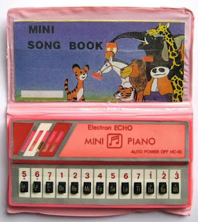 Pequeno piano que era capaz de reproduzir canções variadas. Sucesso da infância nos anos 80 e 90.