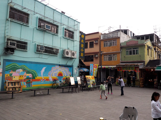 Town square with colourful mural and children playing in Tai O fishing village, Lantau Island, Hong Kong