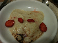 a stack of heart shaped pancakes with sliced strawberries and maple syrup 
