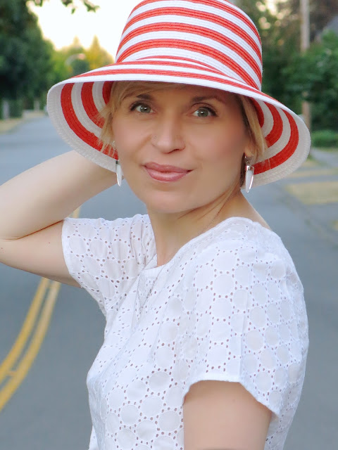 a white eyelet crop top and orange striped hat