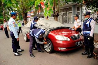 petugas dishub saat menegembosi mobil yang parkir sembarangan