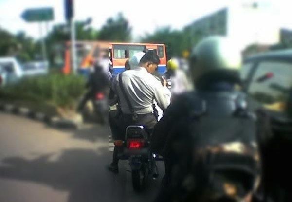 Polisi tidak pakai helm saat naik motor-1
