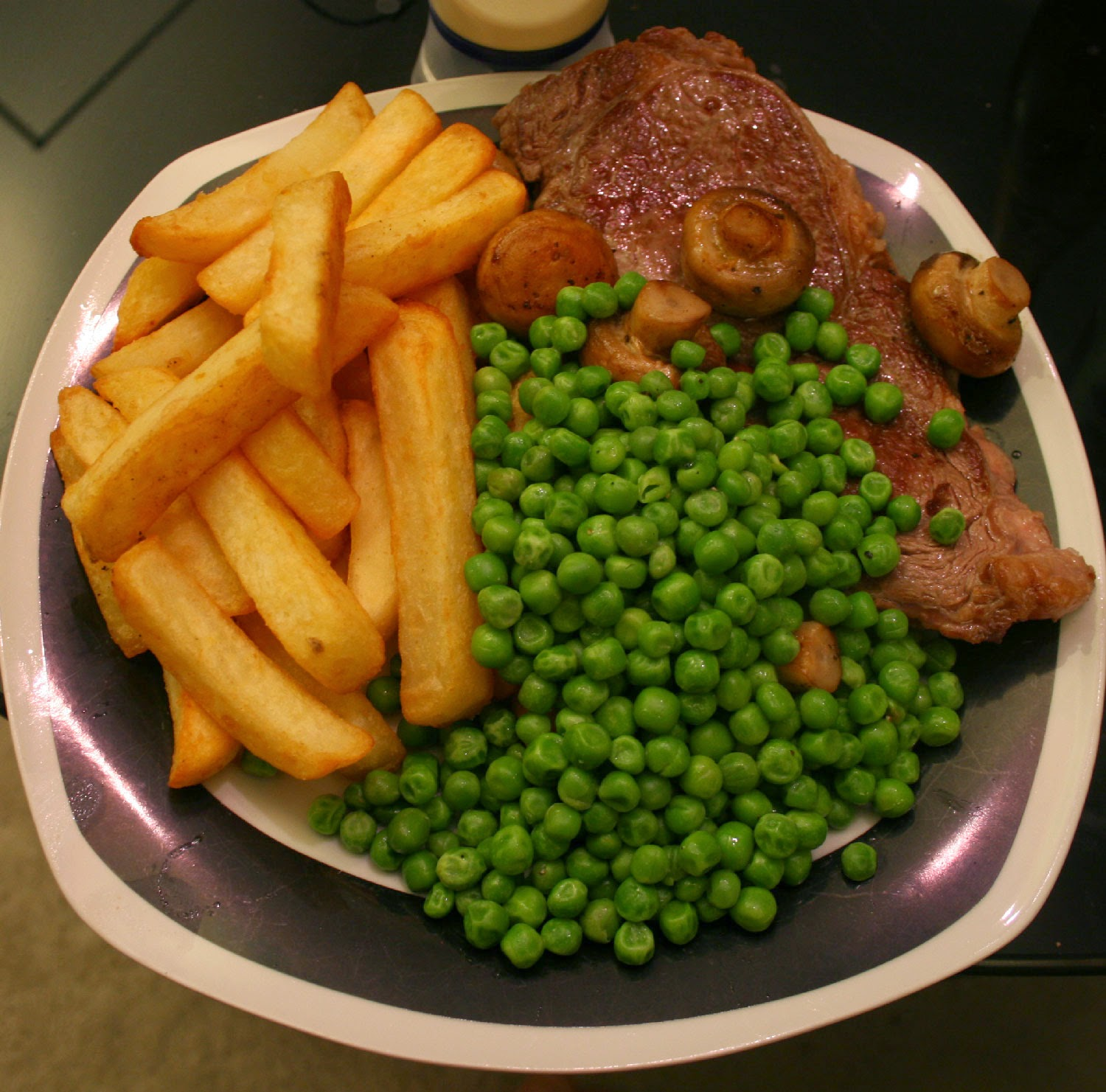 Steak and chips with peas and mushrooms