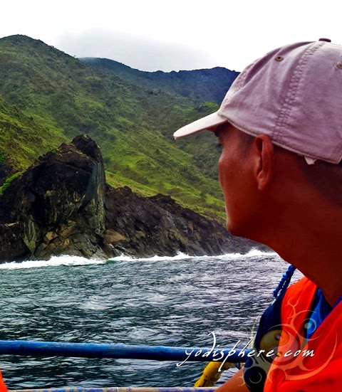 Man looking out on a rocky island hover_share