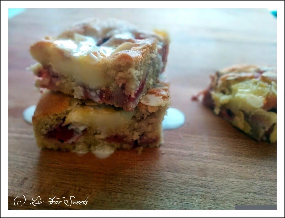 Der fertige Butterkuchen mit Erdbeeren und Puddingflecken in kleinen Stücken übereinander gestapelt und mit Vanillesoße übergossen.
