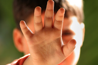 A child abuse victim hold up his hand to the camera.