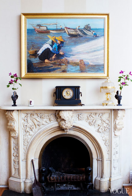 Traditional fireplace mantel with striped walls, a traditional oil painting and antique clock