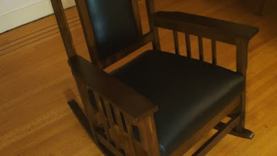 Morris style wooden rocking chair with black leather seat and back on hardwood floor