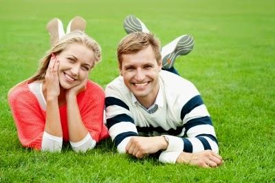 pareja sonriendo acostada en la grama cesped