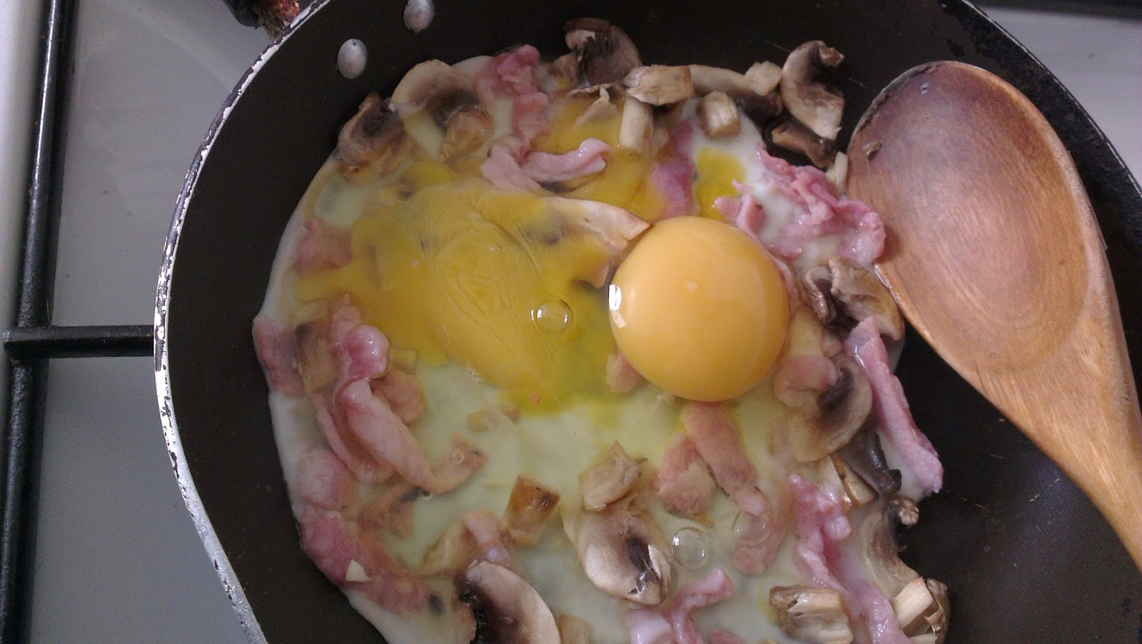 Adding the eggs to the almost cooked mushrooms and bacon