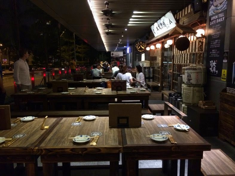 Wooden tables and chairs outside of The Public Izakaya