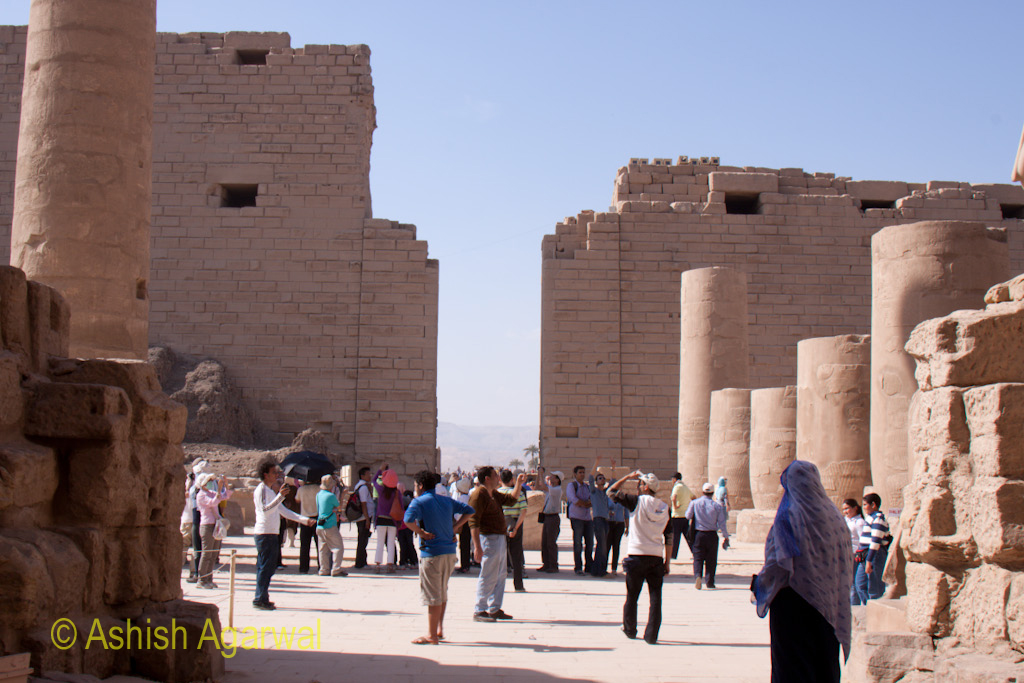 People walking among the remains of the Karnak temple in Luxor