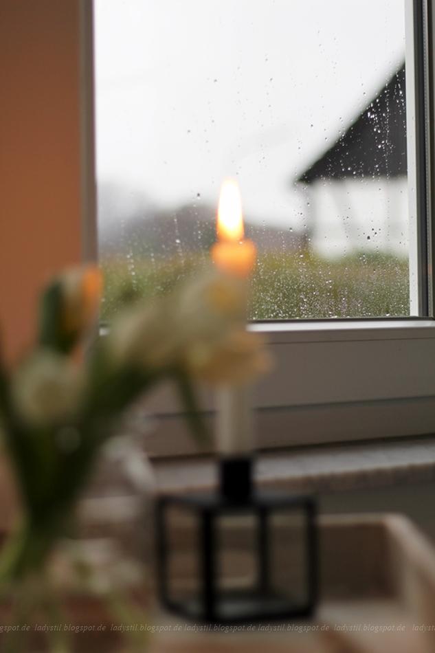 Zoom auf eine vom Regen besprenkelte Fensterscheibe