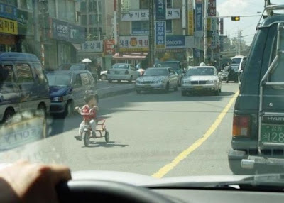 little boy play on the highway with his bicycle