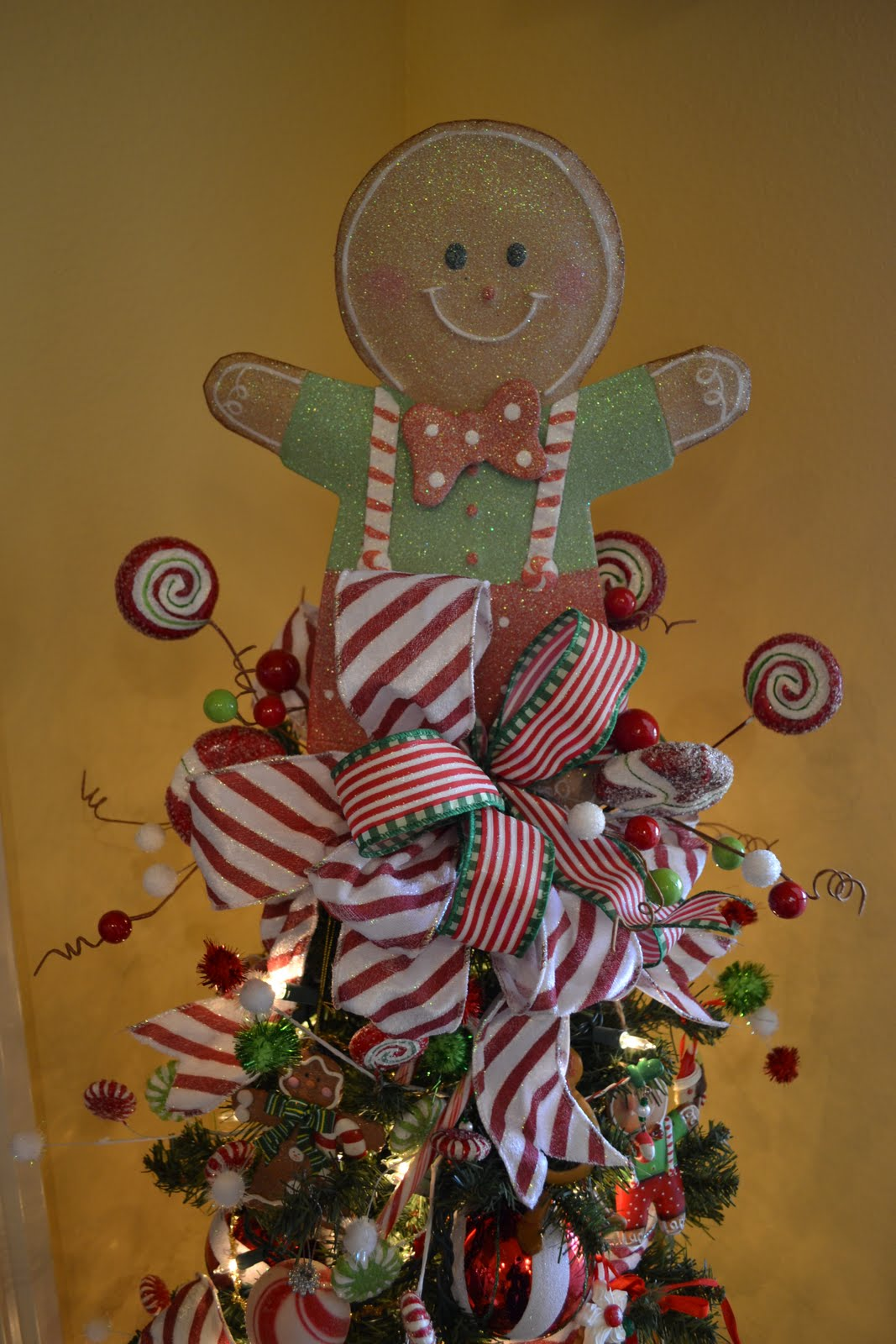 The tree is filled with gingerbread men ribbon candy balls and picks