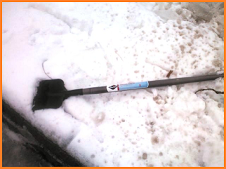 Ice chisel with black blade and gray handle sitting on snow