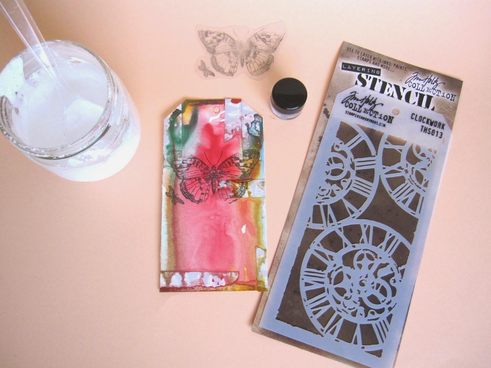 tercer paso tag marzo Celebrating Springtime: tag con embossing de mariposa, polvos emboss color azul, pasta de modelar casera y Stencil Tim Holtz Clockwork
