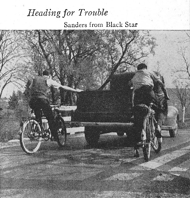 Two boys on bicycles holding onto the back of a truck for a pull