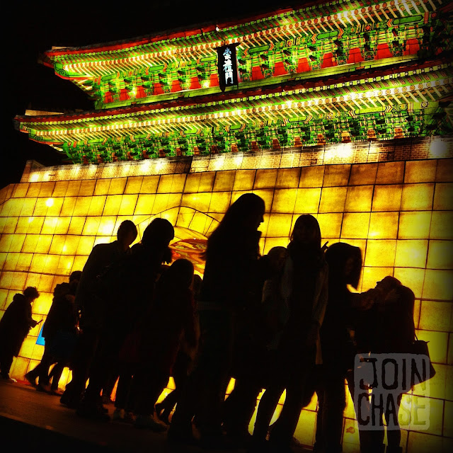 People walking around Seoul Lantern Festival at night.