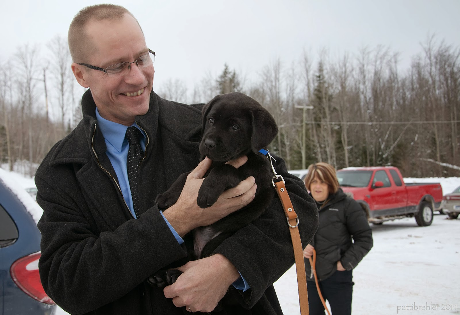 An outside shot in a parking lot (a red truck is in the background on the right) of a man with a buzz cut and glasses, wearing a black coat, is holding a small black lab puppy in his arms. The man is looking at the puppy with a huge smile on his face. A short brown haired woman is in the background behind him.