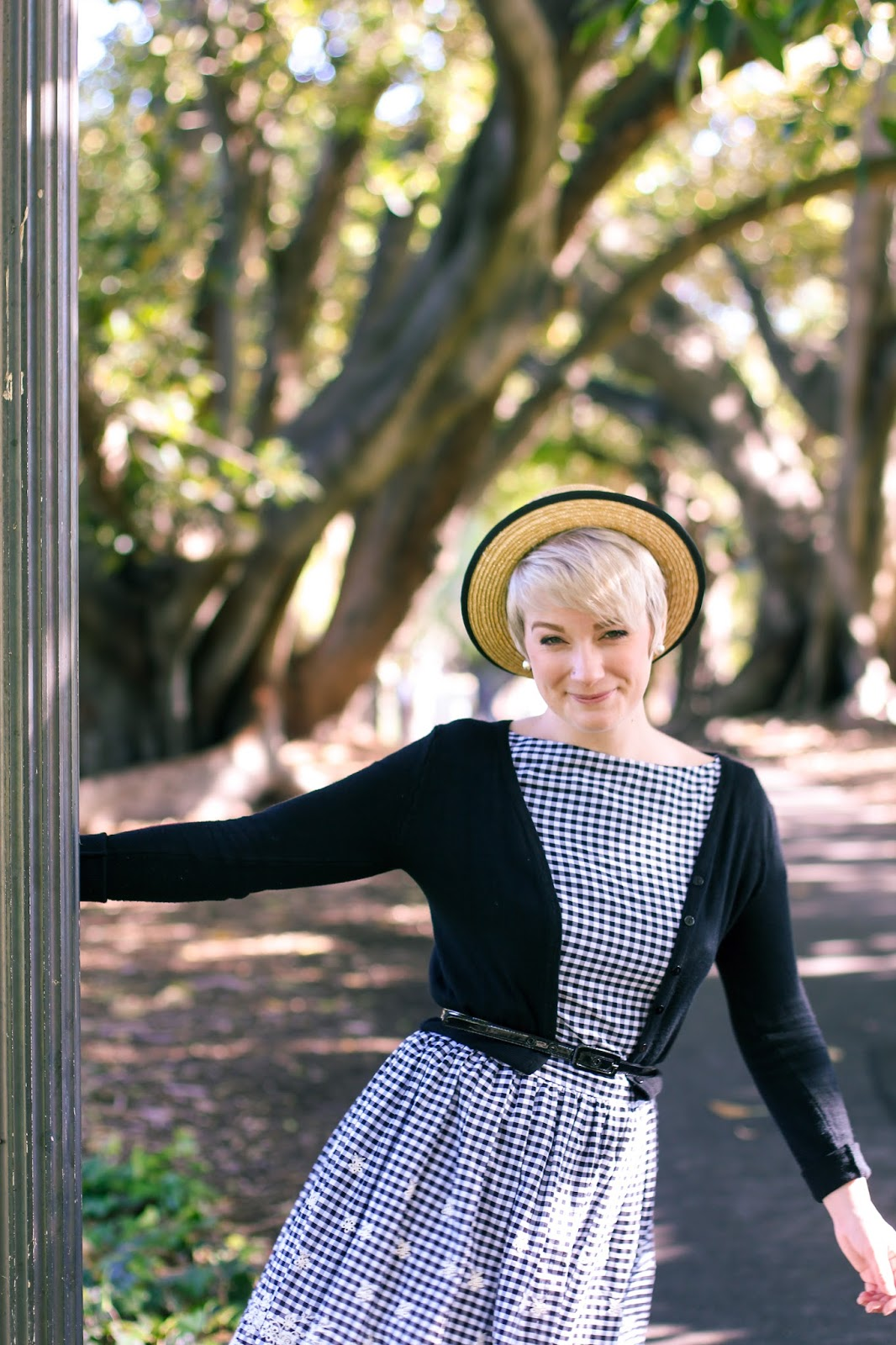 Liana of Finding Femme wears Wheels and Dollbaby Holiday in Nice dress in black and white gingham with black cardi and straw boater hat at Hyde Park in Perth.