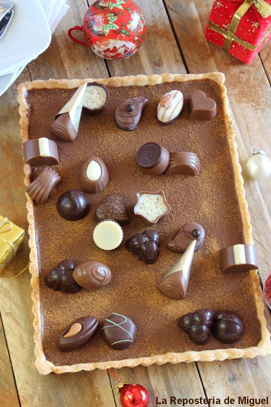 Tarta de masa brisa con relleno de ganaché de chocolate negro y sobre él u surtido de bombones, adornando la mesa de madera bolas y regalos de navidad.