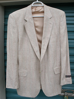 Light tan or cream, lightweight sport jacket with two front pockets and a tan silk lining. Two buttons and average-size lapels. Looks very clean and unwrinkled and spiffy.