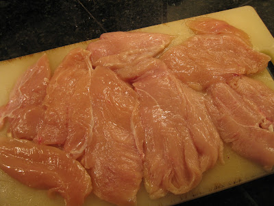 several chicken breasts on cutting board